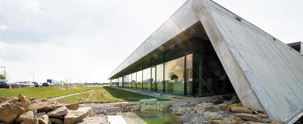 """Das Solera Firmengebäude """"Die Schräge"""" mit dem kleinen Bachlauf und der Glasfront"""